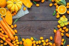 感恩秋天橙色背景、在黑暗的木背景的品种水果和蔬菜与文本的自由空间 库存图片