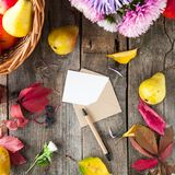 感恩背景用季节性果子、花、贺卡和信封在一张土气木桌上 秋天收获概念 图库摄影