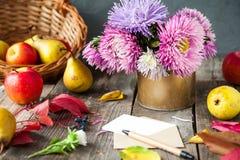 感恩背景用季节性果子、花、贺卡和信封在一张土气木桌上 秋天收获概念 免版税库存图片