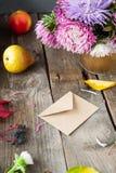 感恩背景用季节性果子、花和工艺纸信封在一张土气木桌上 秋天收获概念 C 免版税库存照片