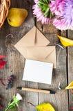 感恩背景用季节性果子,花,贺卡,少量制作在一张土气木桌上的信封 秋天收获 图库摄影