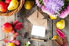 感恩背景用季节性果子,花,贺卡,少量制作在一张土气木桌上的信封 秋天收获 免版税库存照片