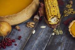 感恩背景:玉米、南瓜饼和下落的叶子在木背景 免版税库存图片