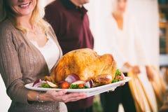感恩:拿着盛肉盘用烘烤土耳其和Garnis的妇女 免版税库存照片