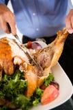 感恩:雕刻晚餐的大火鸡腿的人 免版税库存图片