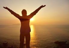 感激的对日出的妇女开放胳膊 免版税库存照片