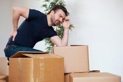 感觉后背疼痛抽疯的人移动重的箱子 免版税库存照片