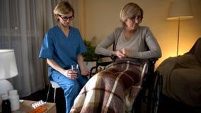 感觉思乡病拒绝的年长夫人采取从护士的医学递悲伤 库存照片