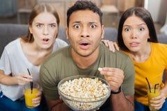 感觉情感的朋友惊奇和惊吓,当观看恐怖片时 免版税库存照片