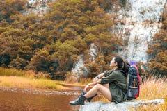 感觉战胜开会的远足者妇女在河在秋天森林里和野营附近放松在假日 库存照片