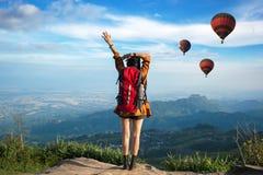 感觉战胜饰面和看见气球的远足者妇女 免版税库存照片