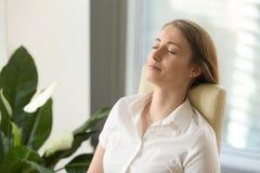 感觉放松的倾斜在办公室cha的镇静可爱的妇女 免版税图库摄影
