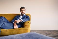 感觉放松 英俊和穿着体面的商人基于沙发并且考虑事务 库存照片