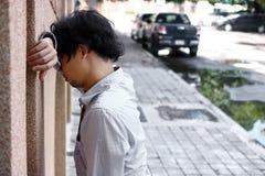 感觉沮丧的被注重的年轻亚裔的商人失望在外部办公室 免版税库存照片
