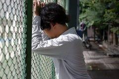 感觉沮丧的被注重的年轻亚裔的商人失望在外部办公室 库存图片