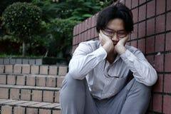 感觉沮丧的被注重的年轻亚裔的商人失望 失业的商人概念 库存图片