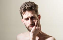 感觉牙痛 接触他的面颊的沮丧的人早晨 有胡子的人需要胡子理发师 修饰私有 图库摄影