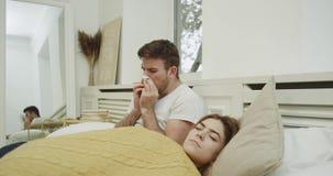 感觉的年轻人的流感时间非常坏他是在与他的妇女的床上,并且有一坏鼻涕,妇女有睡眠 影视素材