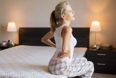 感觉背部疼痛的妇女在家睡觉在床上以后 库存图片