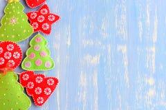 感觉绿色和红色圣诞树,球,在蓝色木背景的星装饰品与文本的拷贝空间在右边 库存图片
