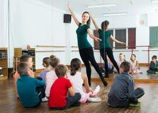 感兴趣的排练芭蕾的男孩和女孩在演播室跳舞 免版税库存照片