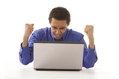 愤怒呼喊在他的膝上型计算机的蓬松卷发人 免版税库存照片