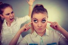 愤怒女孩尖叫对她的朋友,女性结束他的耳朵 图库摄影