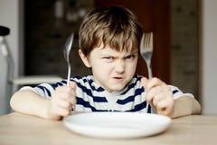 愤怒的小男孩等待的晚餐 免版税库存照片