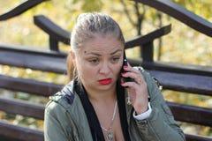 愤怒的,惊奇的女孩在电话谈话户外 库存照片