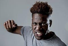 愤怒的年轻可爱的非裔美国人的黑人威胁猛击与在恼怒的翻倒的拳头 免版税库存照片