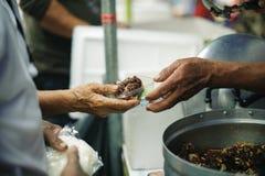 慈善食物是没有金钱贫寒的希望:乞求食物的概念:志愿者对解除的贫寒的份额食物 免版税库存图片
