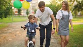 慈爱的父母在城市公园教儿子逗人喜爱的男孩骑自行车,孩子循环,并且他的父亲拿着他 股票视频