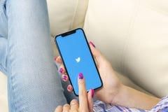 慌张在苹果计算机iPhone x智能手机屏幕特写镜头的应用象在妇女手上 慌张app象 社会媒介象 社会 图库摄影
