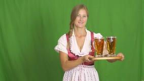 慕尼黑啤酒节女孩在绿色背景4k的一张木桌上把两杯啤酒放 影视素材