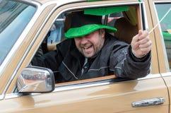 慕尼黑,巴伐利亚,德国- 2016年3月13日:关闭在他的汽车有爱尔兰旗子的和帽子的一个欢呼的人圣帕特里克` s天 图库摄影