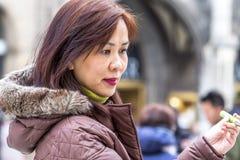 慕尼黑,德国- 2018年2月15日:采取与她的智能手机的亚裔夫人selfies 免版税库存图片