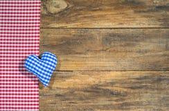 慕尼黑啤酒节、蓝色巴法力亚心脏和红色土气方格的织品的背景在木头 免版税库存图片