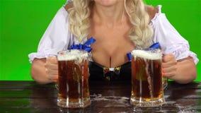 慕尼黑啤酒节女孩在一张木桌上把两杯啤酒放 绿色屏幕 慢的行动 影视素材