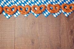 慕尼黑啤酒节节日与巴法力亚旗子样式的背景用椒盐脆饼和餐巾 免版税库存照片