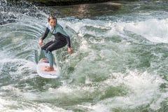 慕尼黑- 8月08 :一位未认出的女性冲浪者工作波浪在海浪&样式2015年8月08日在慕尼黑 免版税库存照片