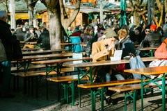 慕尼黑,德国, 2016年12月29日:一个年轻人在街道咖啡吃用快餐和全国食物在中央附近 库存照片
