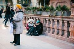 慕尼黑,德国, 2016年12月29日:两个低劣的女孩在中心广场坐并且吃在慕尼黑 亚文化群 每天 库存照片