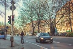 慕尼黑,德国, 2016年12月29日:汽车和自行车骑士站立在一个红绿灯在慕尼黑 城市生活 日常生活 库存图片