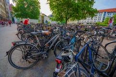 慕尼黑,德国- 2015年7月30日:与站立不计其数的自行车的阴部的自行车停车处驻地排队 库存图片