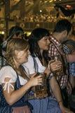 慕尼黑,德国- 2016年9月18日:慕尼黑啤酒节慕尼黑:传统服装的2个女孩喝在啤酒亭子的 免版税库存照片