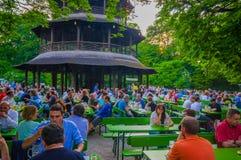 慕尼黑,德国- 2015年7月30日:著名地方Chinesischer Turmgarden,享用到处都是的人喝在a的啤酒 库存图片