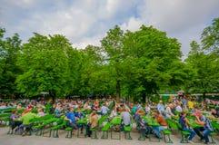 慕尼黑,德国- 2015年7月30日:著名地方Chinesischer Turmgarden,享用到处都是的人喝在a的啤酒 图库摄影