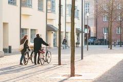 慕尼黑, 2017年10月29日:有自行车的两个人步行沿着向下街道的 免版税库存图片