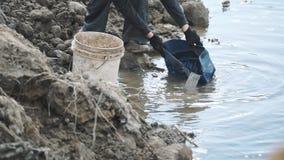 慢动作与塑料桶的人凹道肮脏的水从在建筑工地的沟槽 股票录像