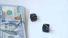 慢动作两黑模子,胡扯,投掷在白色背景,在一盒美元附近, 赌博的概念 股票录像